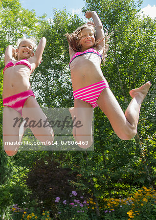 Girls in swimming costume jumping in garden Stock Photo - Premium Royalty-Free, Image code: 614-07806469