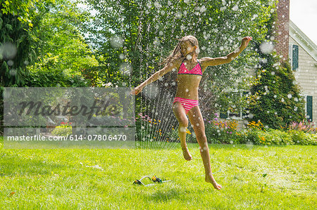 Girl in swimming costume jumping over garden sprinkler Stock Photo - Premium Royalty-Free, Image code: 614-07806470