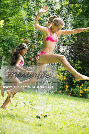Girls in swimming costume jumping over garden sprinkler Stock Photo - Premium Royalty-Free, Image code: 614-07806471
