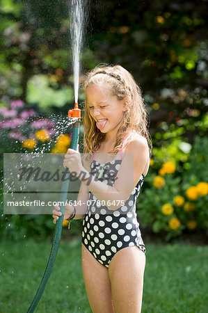 Girl in swimming costume playing with garden hose Stock Photo - Premium Royalty-Free, Image code: 614-07806475