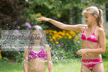 Girls in swimming costume playing with garden sprinkler Stock Photo - Premium Royalty-Free, Image code: 614-07806476