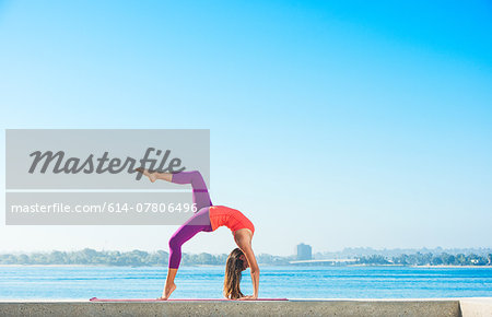 Young woman practicing yoga position at Pacific beach, San Diego, California, USA Stock Photo - Premium Royalty-Free, Image code: 614-07806496