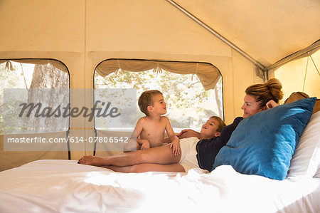 Mother and two sons reclining on tent bed whilst glamping, County Park, Los Angeles, California, USA Stock Photo - Premium Royalty-Free, Image code: 614-07806542