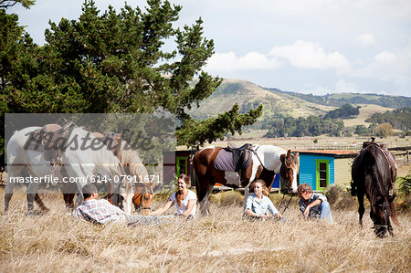Horse riders taking break on grass, Pakiri Beach, Auckland, New Zealand Stock Photo - Premium Royalty-Free, Image code: 614-07911671