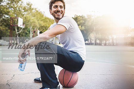 Portrait of young male basketball sitting on ball Stock Photo - Premium Royalty-Free, Image code: 614-07911677