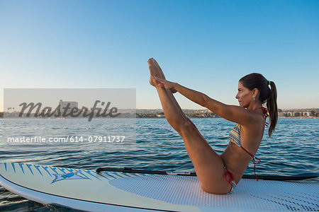 Mature woman in yoga position on paddleboard, Mission Bay, San Diego, California, USA Stock Photo - Premium Royalty-Free, Image code: 614-07911737