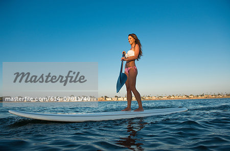 Young woman stand up paddleboarding, Mission Bay, San Diego, California, USA Stock Photo - Premium Royalty-Free, Image code: 614-07911740