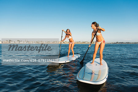 Two women chatting whilst stand up paddleboarding, Mission Bay, San Diego, California, USA Stock Photo - Premium Royalty-Free, Image code: 614-07911741