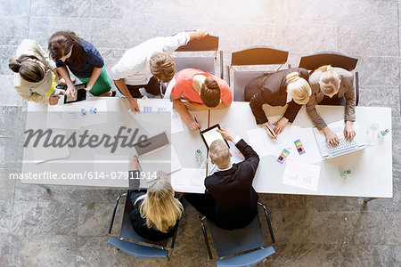 Overhead view of business team brainstorming at desk in office Stock Photo - Premium Royalty-Free, Image code: 614-07911914
