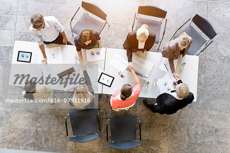 Overhead view of business team meeting clients at desk in office Stock Photo - Premium Royalty-Free, Image code: 614-07911916