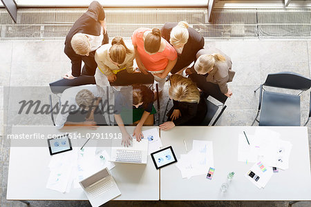 Overhead view of huddled business team meeting at desk in office Stock Photo - Premium Royalty-Free, Image code: 614-07911918