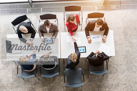 Overhead view of business team shaking hands with client at desk in office Stock Photo - Premium Royalty-Free, Image code: 614-07911925