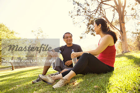 Mature running couple taking a break and drinking water in park Stock Photo - Premium Royalty-Free, Image code: 614-07911958