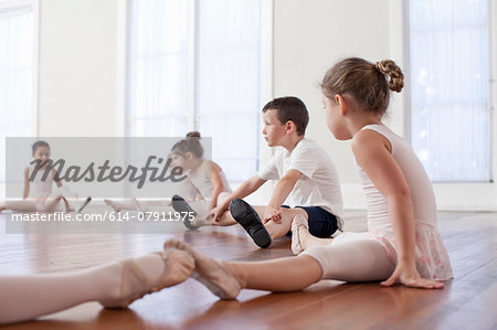 Children sitting on floor practicing ballet position in ballet school Stock Photo - Premium Royalty-Free, Image code: 614-07911975