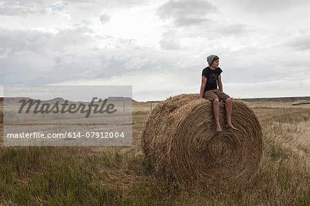 Teenage boy sitting on haystack in field, South Dakota, USA Stock Photo - Premium Royalty-Free, Image code: 614-07912004