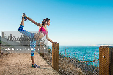 Young woman doing stretches on path by sea Stock Photo - Premium Royalty-Free, Image code: 614-07912033