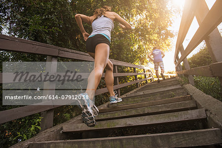 Mid adult man and young woman running up steps, rear, low angle view Stock Photo - Premium Royalty-Free, Image code: 614-07912038
