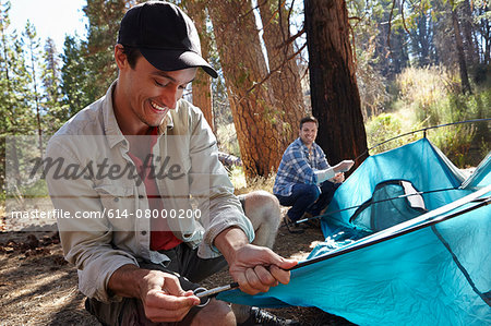 Two young male campers putting up tent in forest, Los Angeles, California, USA Stock Photo - Premium Royalty-Free, Image code: 614-08000200