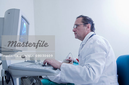 Sonographer looking at ultrasound scan on computer screen whilst scanning Stock Photo - Premium Royalty-Free, Image code: 614-08030609
