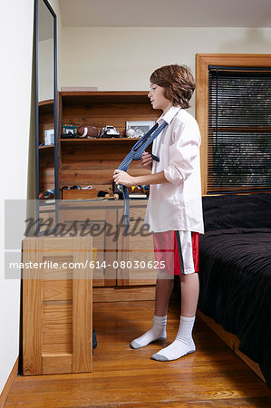 Boy practicing tying large tie in bedroom mirror Stock Photo - Premium Royalty-Free, Image code: 614-08030625