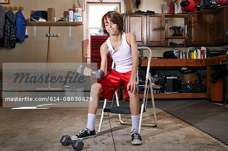 Slim boy struggling to lift hand weight in garage Stock Photo - Premium Royalty-Free, Image code: 614-08030629