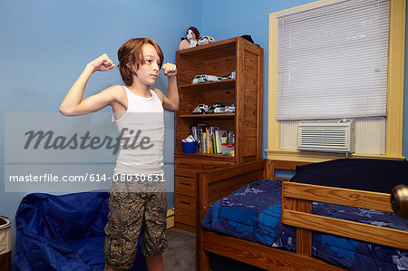 Slim boy flexing arm muscles in bedroom Stock Photo - Premium Royalty-Free, Image code: 614-08030631