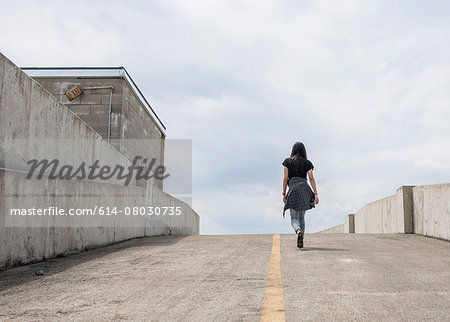 Young woman walking up car park ramp Stock Photo - Premium Royalty-Free, Image code: 614-08030735