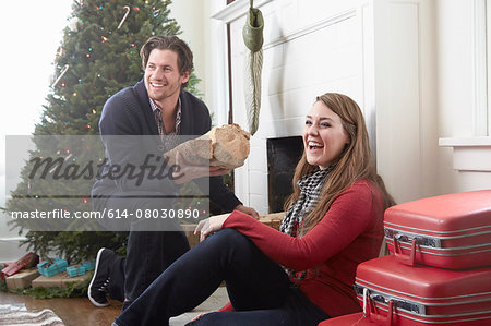 Young couple preparing log fire at christmas Stock Photo - Premium Royalty-Free, Image code: 614-08030890