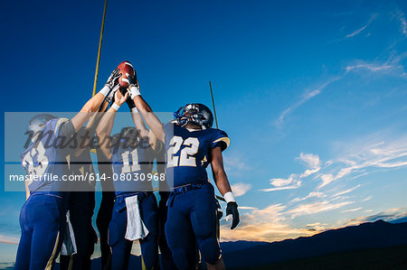 Teenage and young male american football team celebrating and holding up ball Stock Photo - Premium Royalty-Free, Image code: 614-08030968