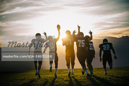 Rear view of teenage and young male american football team celebrating at sunset Stock Photo - Premium Royalty-Free, Image code: 614-08031108