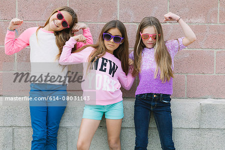 Three girls flexing muscles Stock Photo - Premium Royalty-Free, Image code: 614-08031143