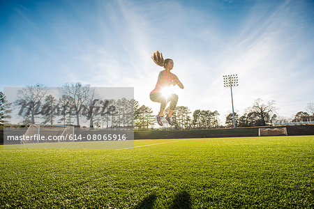 Young female athlete doing jump training on sports field Stock Photo - Premium Royalty-Free, Image code: 614-08065916