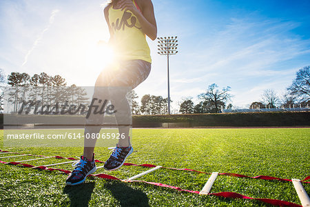 Neck down view of female athlete training with agility ladder on sports field Stock Photo - Premium Royalty-Free, Image code: 614-08065926