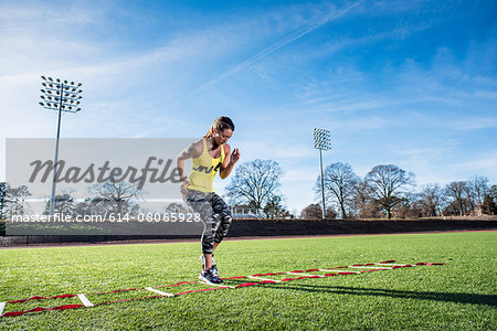 Young female athlete training with agility ladder on sports field Stock Photo - Premium Royalty-Free, Image code: 614-08065928