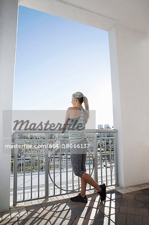 Mature woman in sports clothing looking out from city balcony Stock Photo - Premium Royalty-Free, Image code: 614-08066137