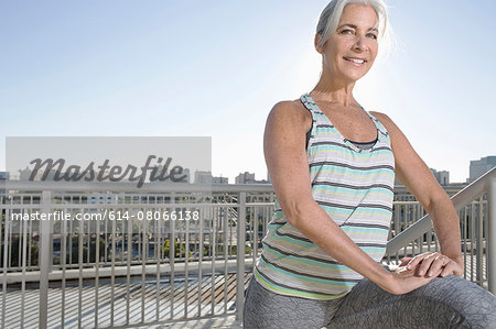 Portrait of mature woman doing warm up exercises on city balcony Stock Photo - Premium Royalty-Free, Image code: 614-08066138