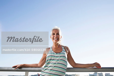 Portrait of mature woman in sports clothing leaning against city balcony Stock Photo - Premium Royalty-Free, Image code: 614-08066139