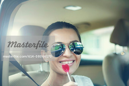Young woman sitting in car, smiling, holding lollypop Stock Photo - Premium Royalty-Free, Image code: 614-08066170