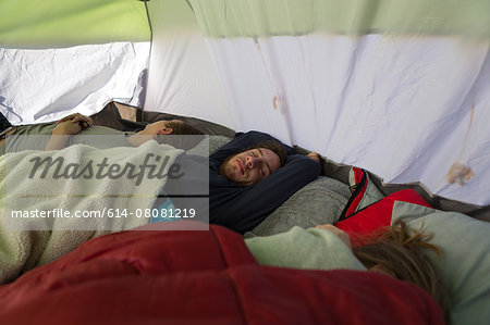 Three young adult friends asleep in tent Stock Photo - Premium Royalty-Free, Image code: 614-08081219