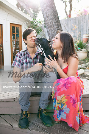 Young couple sitting on patio with dog licking face Stock Photo - Premium Royalty-Free, Image code: 614-08081243