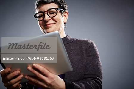 Studio portrait of mature businesswoman reading digital tablet Stock Photo - Premium Royalty-Free, Image code: 614-08081363