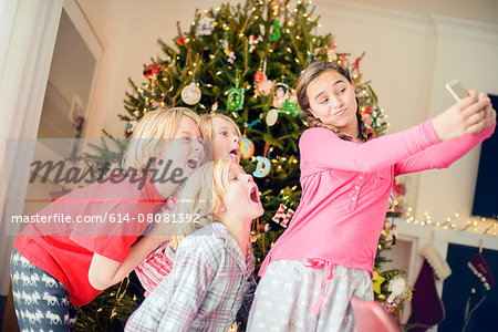 Teenage girl and brothers taking smartphone selfie at christmas Stock Photo - Premium Royalty-Free, Image code: 614-08081392