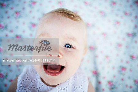 Portrait of smiling baby girl laying on mat Stock Photo - Premium Royalty-Free, Image code: 614-08119547