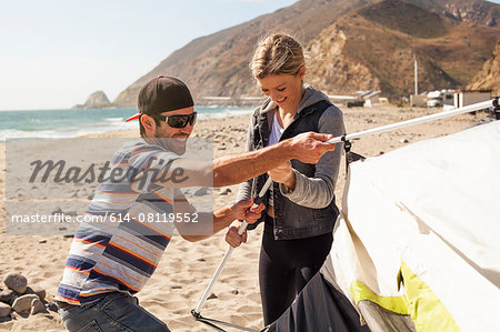 Couple setting up tent on beach, Malibu, California, USA Stock Photo - Premium Royalty-Free, Image code: 614-08119552