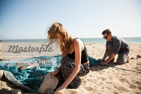 Couple setting up tent on beach, Malibu, California, USA Stock Photo - Premium Royalty-Free, Image code: 614-08119556