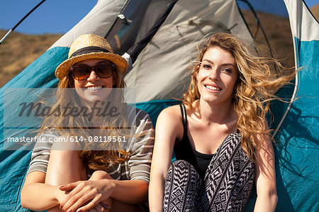Girlfriends relaxing beside tent Stock Photo - Premium Royalty-Free, Image code: 614-08119561