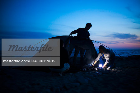 Group of friends setting up tent on beach at sunset Stock Photo - Premium Royalty-Free, Image code: 614-08119615