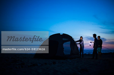 Group of friends setting up tent on beach at sunset Stock Photo - Premium Royalty-Free, Image code: 614-08119616