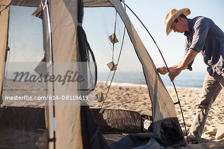 Man setting up tent on beach, Malibu, California, USA Stock Photo - Premium Royalty-Free, Image code: 614-08119619