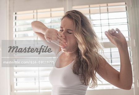 Portrait of a young woman yawning and stretching Stock Photo - Premium Royalty-Free, Image code: 614-08119775